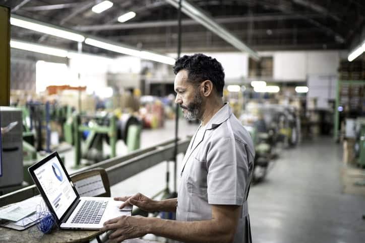 man working on laptop in warehouse