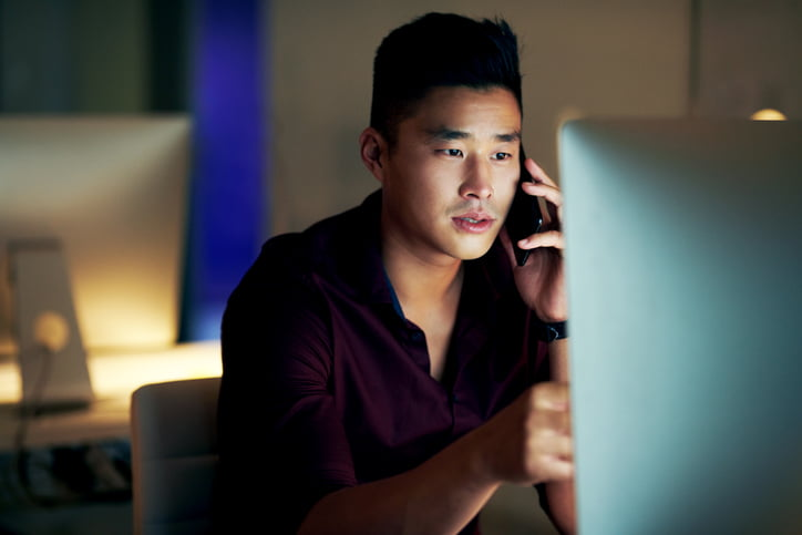 man looking at his computer whilst talking on the phone