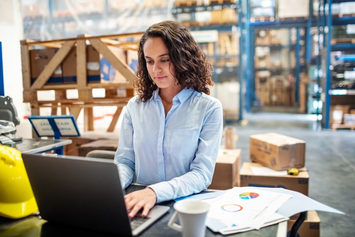 businesswoman working on laptop in warehouse