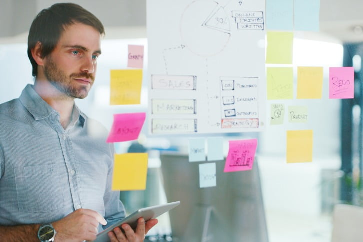 male worker looking at post-it notes