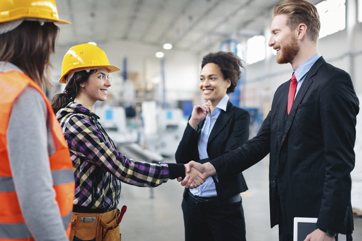 warehouse managers and workers shaking hands